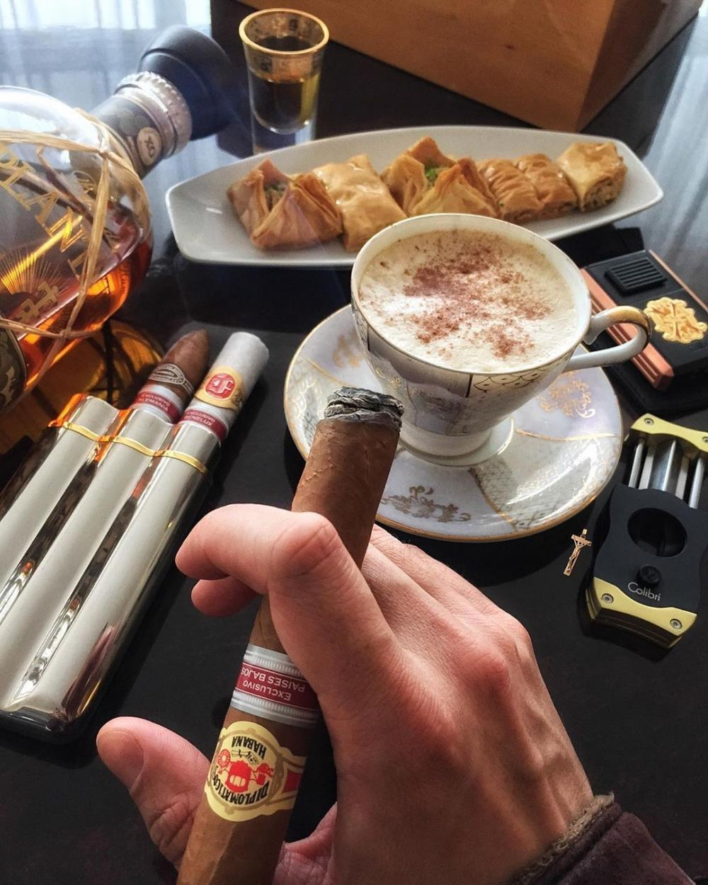Luxurious life. A successful gentleman in an expensive suit with a cigar and a glass of whiskey or a cup of coffee is eye-catching