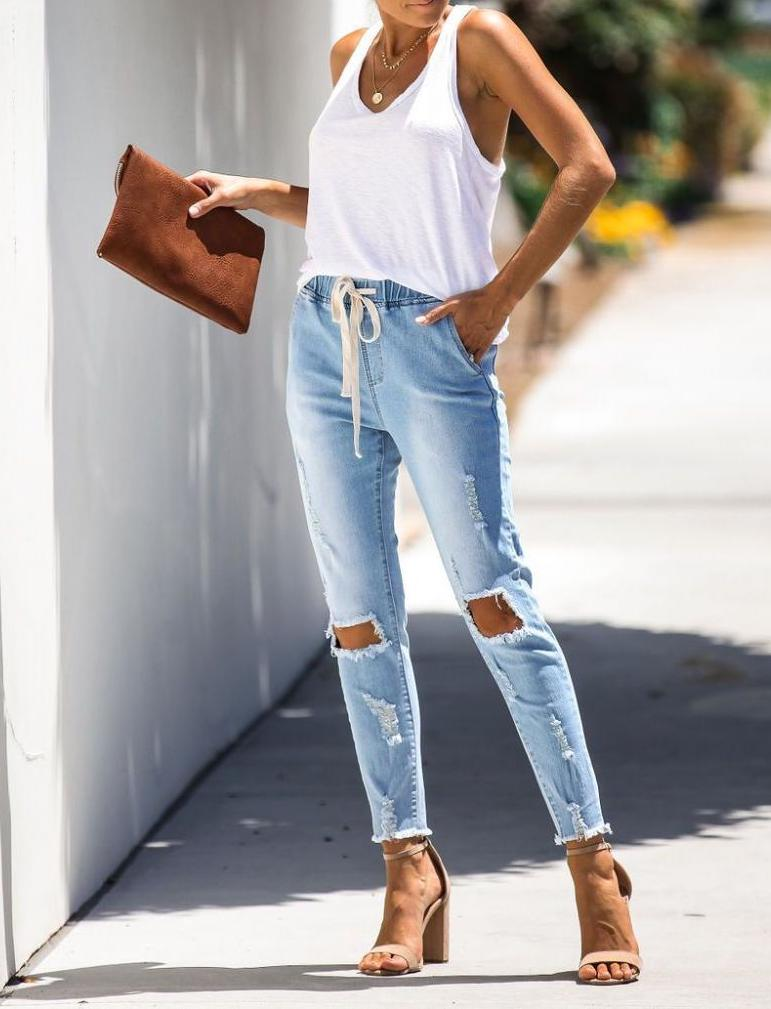 Classic casual summer look with white tank top and blue ripped jeans
