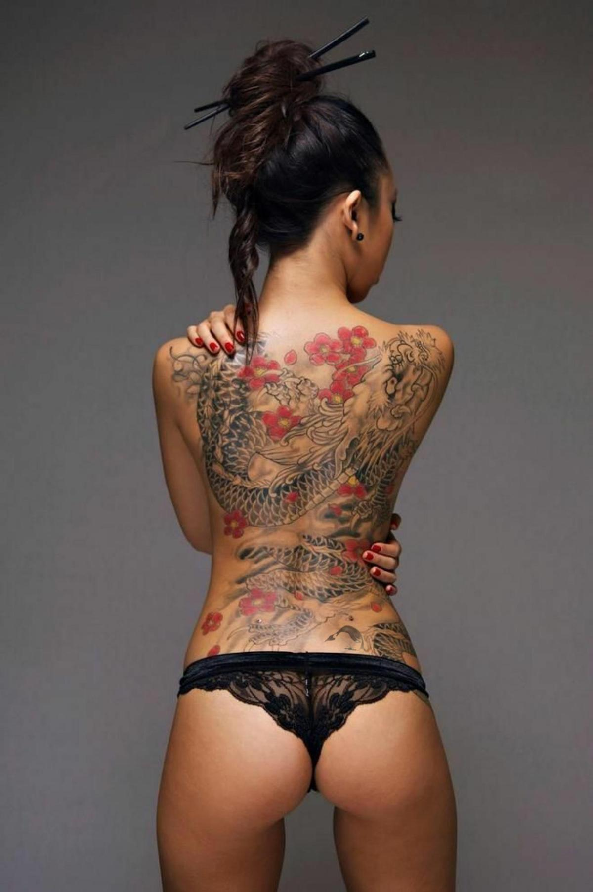Oriental dragon in the sakura blossom tattoo on the girl's back