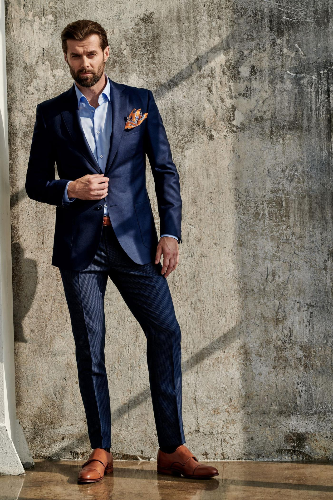 Elegant man in the dark blue suit and brown shoes. Good taste