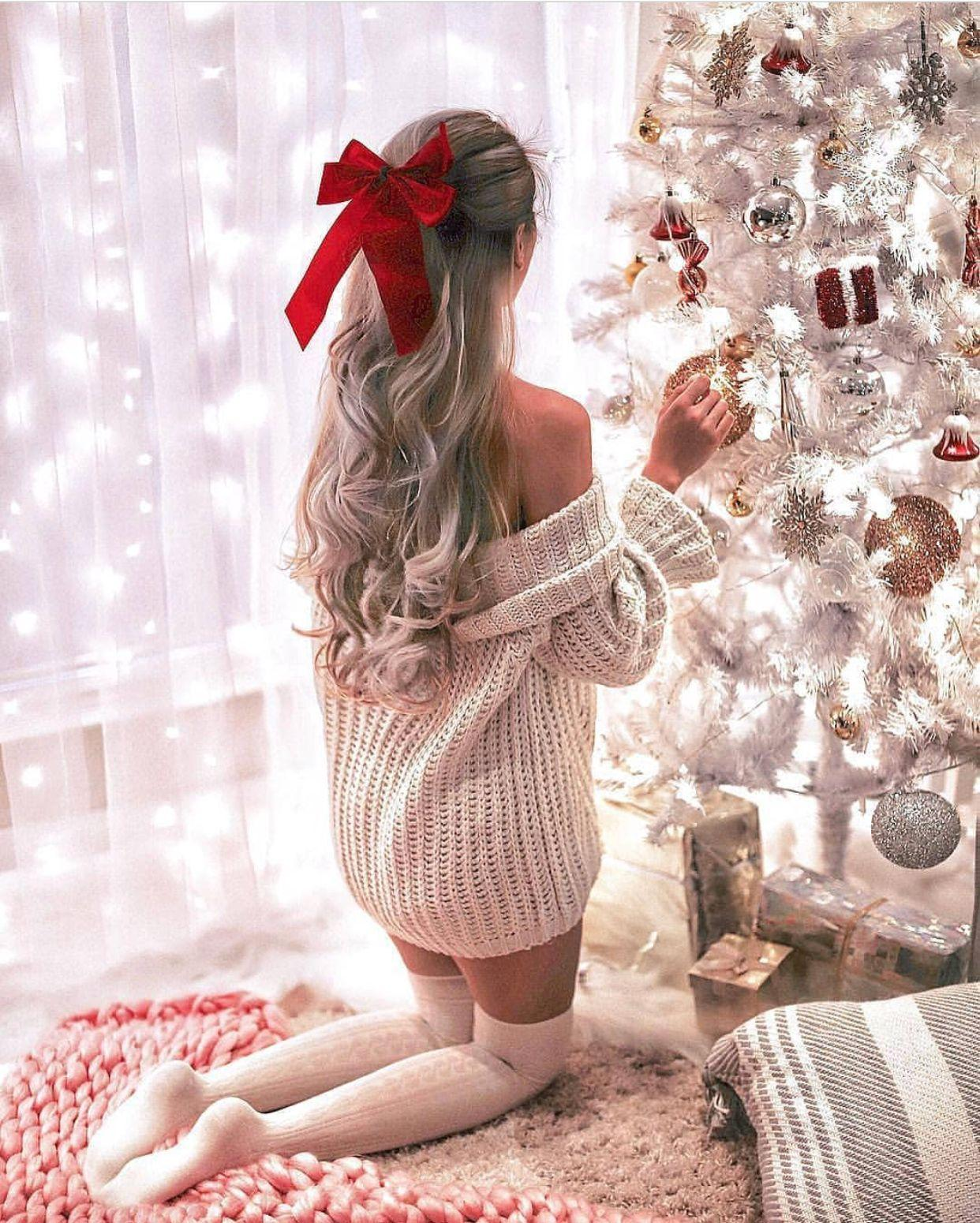 Girl wears sweater and stockings decorating Christmas tree