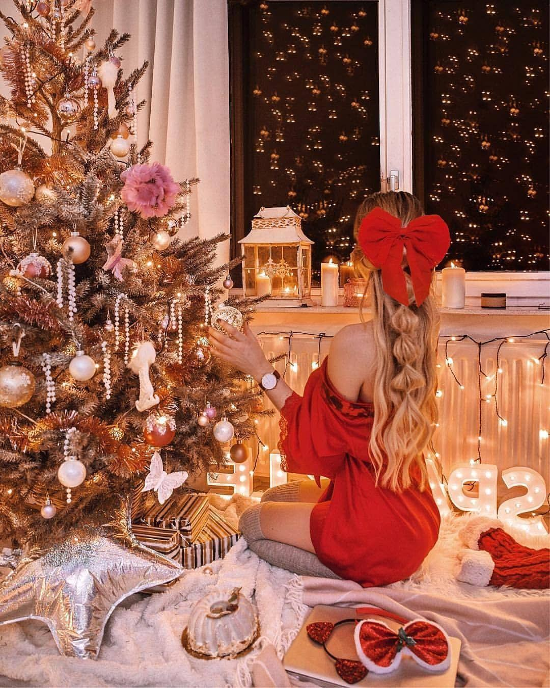 Cute girl in red mini dress with ribbon in hair unpacking Christmas presents