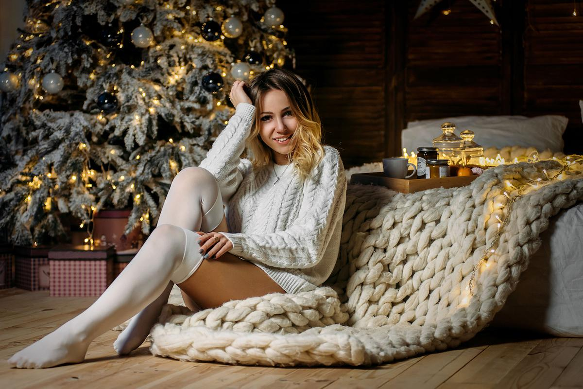 Woman in white sweater and stockings sitting on the plaid near Christmas tree