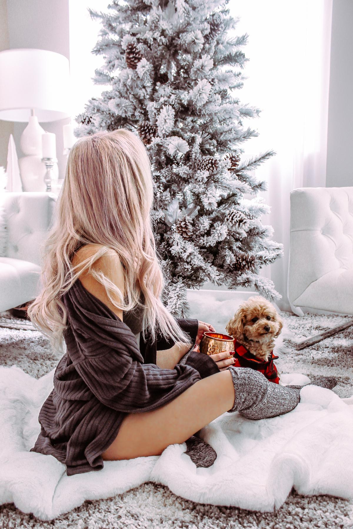 Blond girl in sweater and stockings with her dog sit near Christmas tree