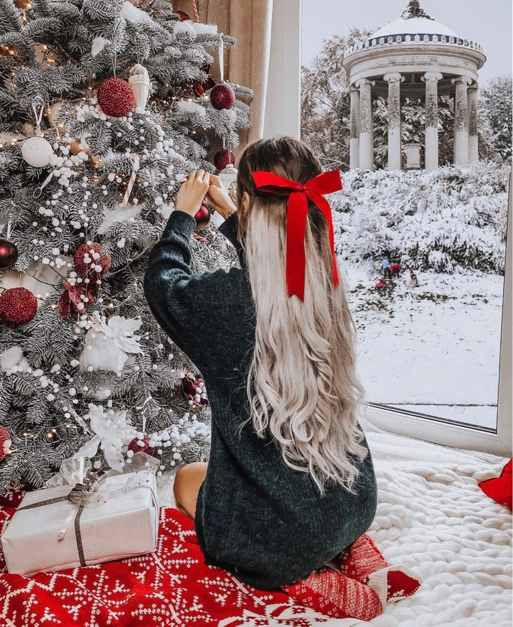Blondie with red ribbon in long hair decorating Christmas tree