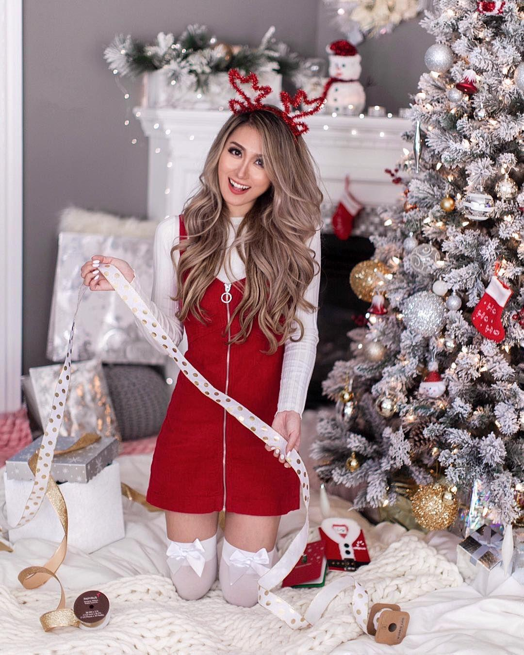 Beautiful girl in deer horns packs Christmas presents near Christmas tree