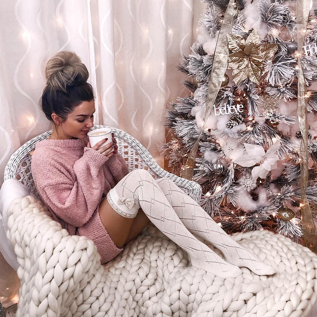 Woman in white stockings drinks hot coffee near Christmas tree