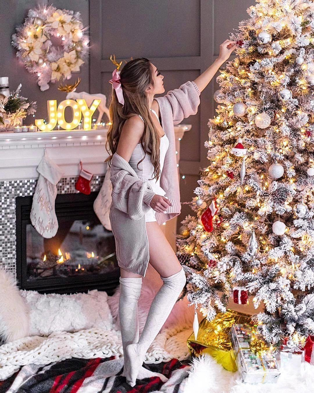 Sexy girl with ribbon in hair in stockings decorating Christmas tree