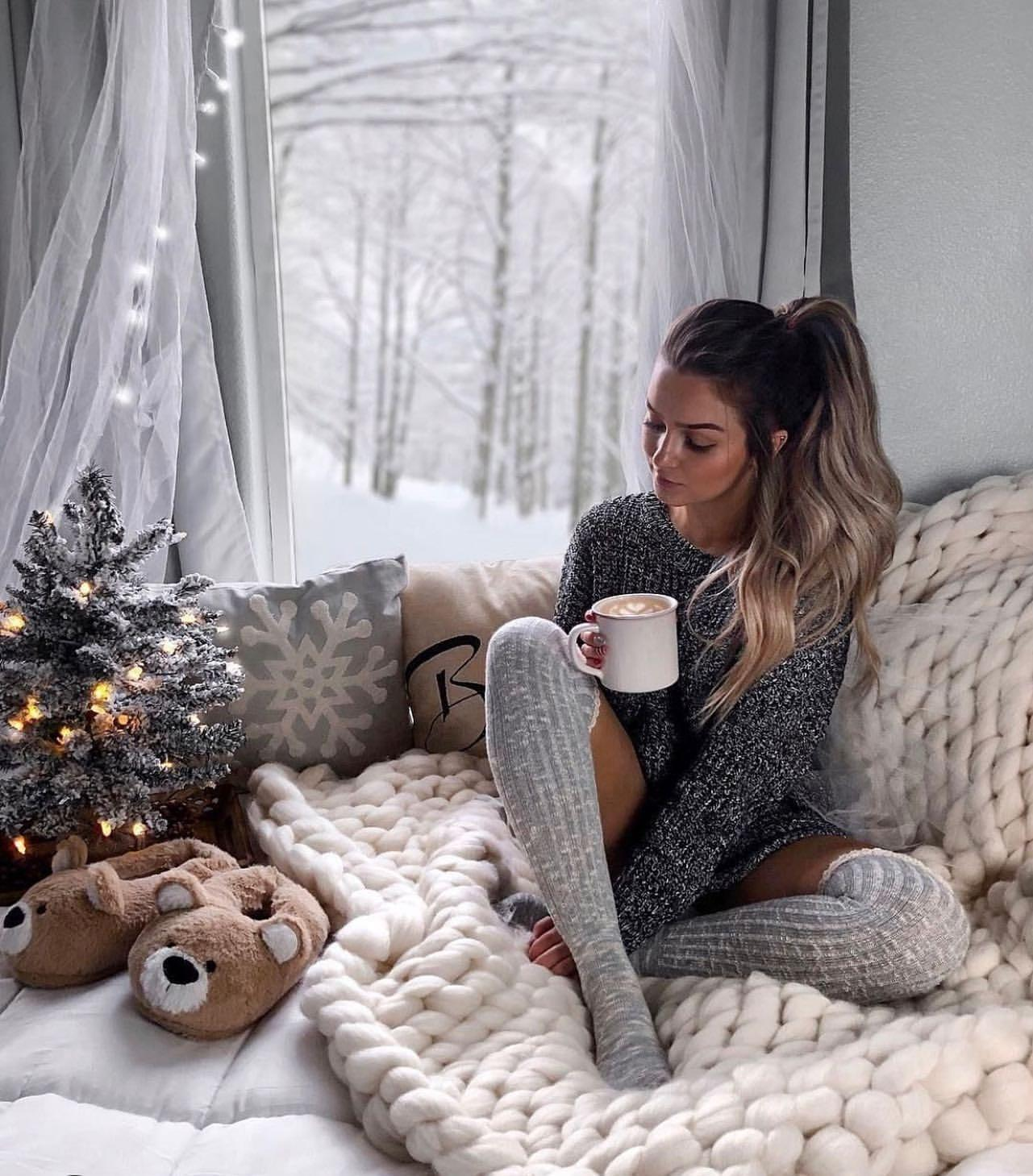 Girl in stockings with cup of coffee near Christmas tree in festive mood