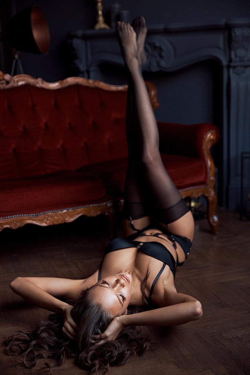 Amazing girl in black lingerie set lies on the floor