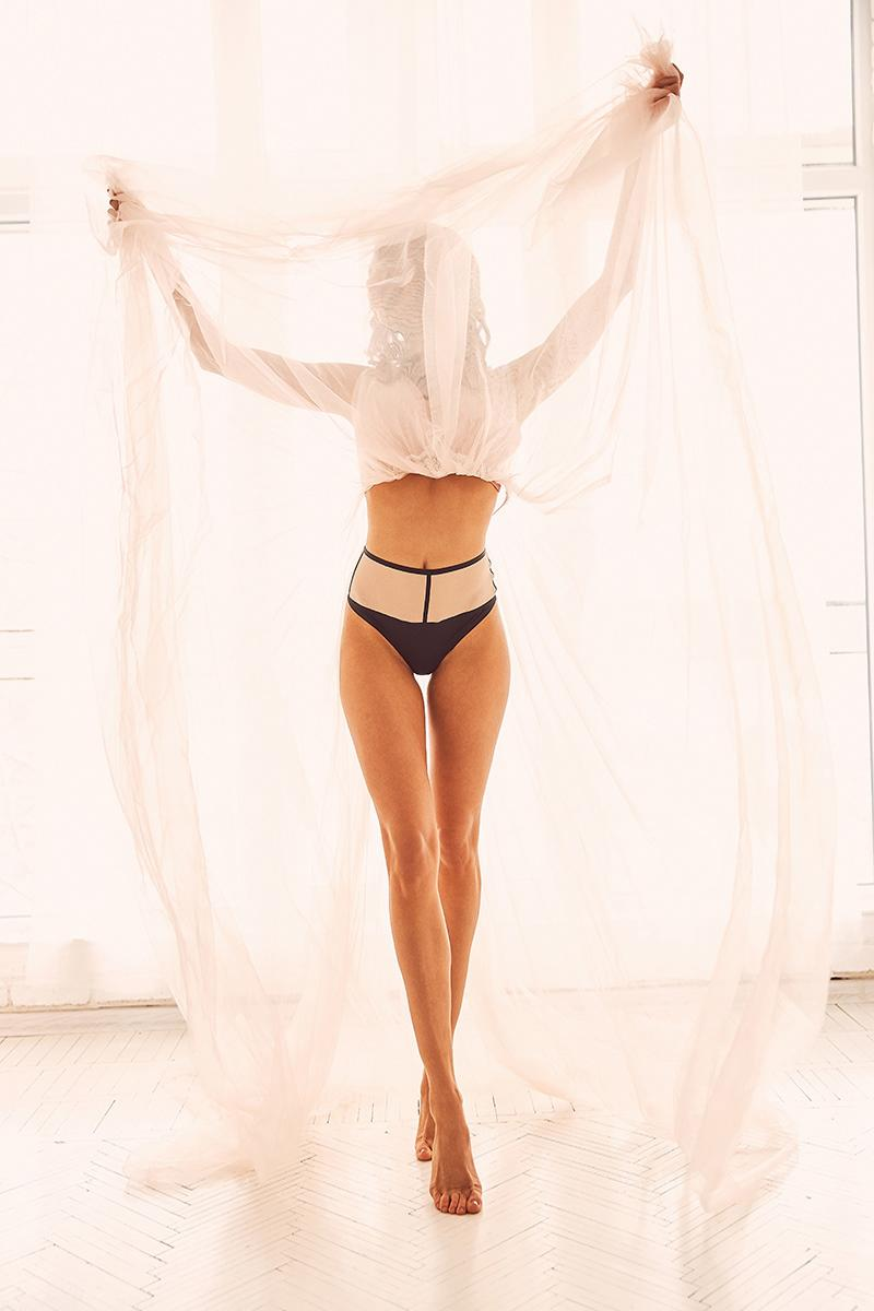 Joyful pose, beautiful legs, woman hiding her face with transparent skirt