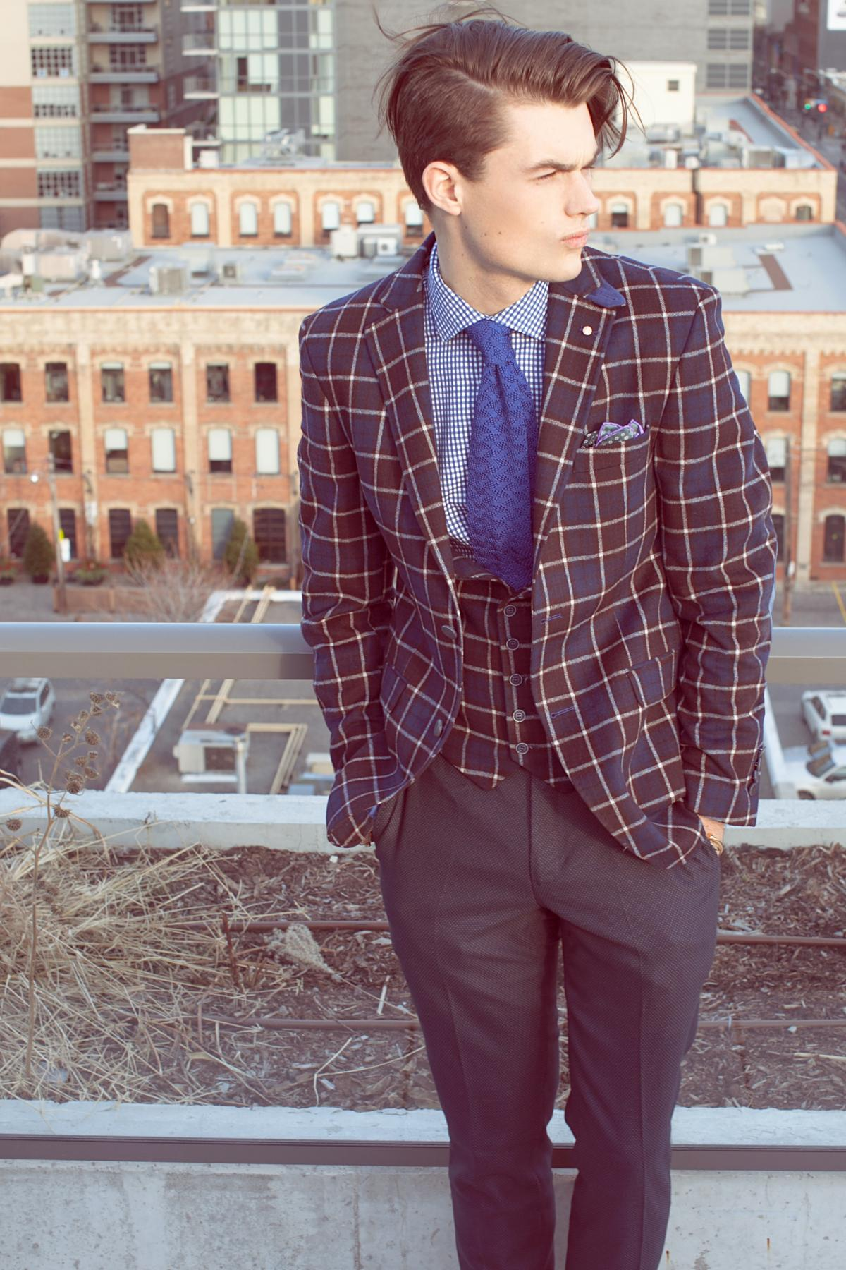 Young man looking awesome in squared jacket with blue tie