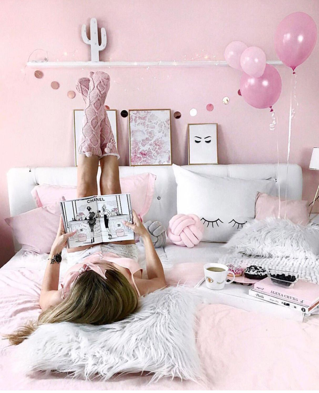 Festive pink mood on the winter holidays. Girl in socks with magazine lies on the bed