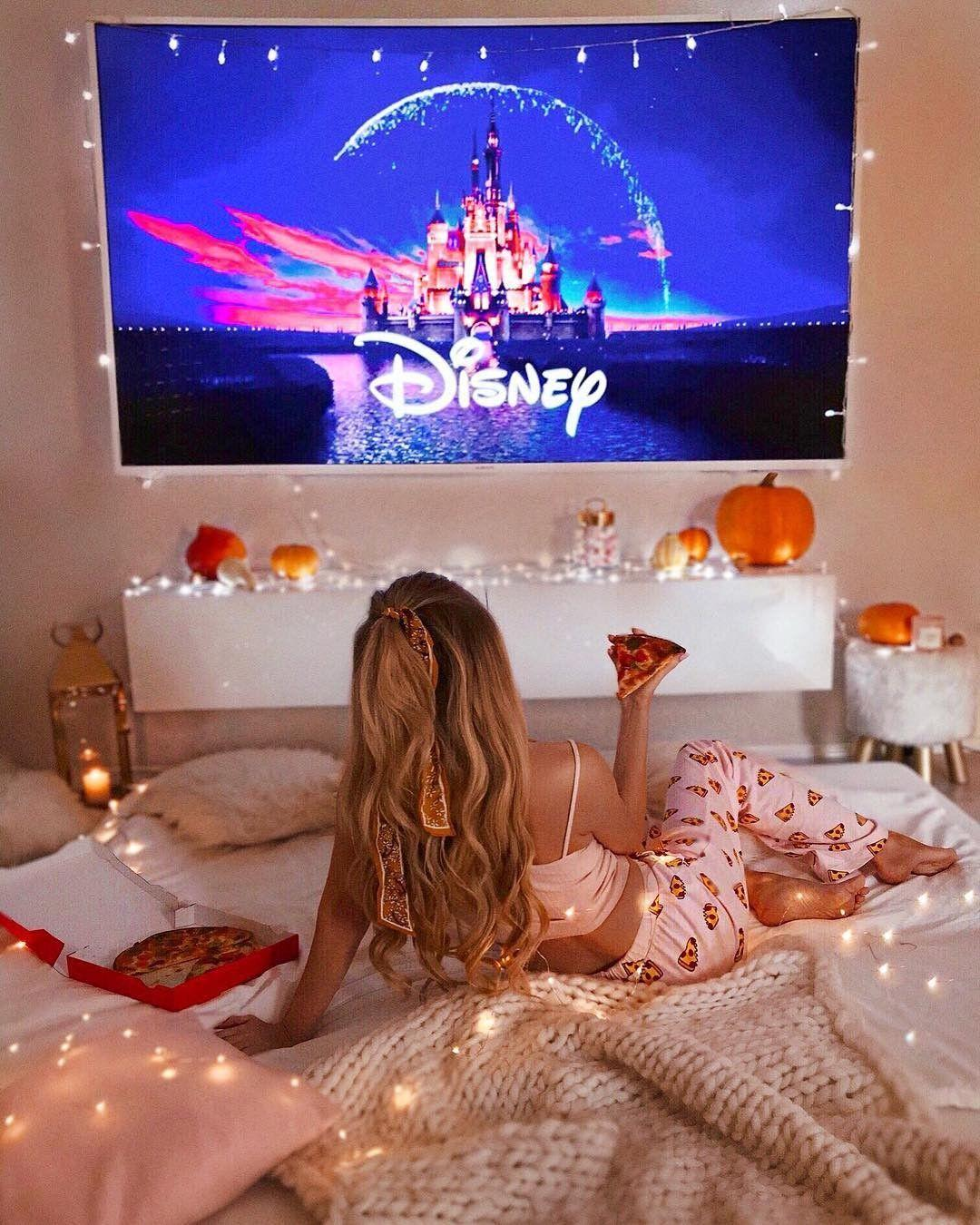 The best holiday time with pizza and TV. Girl lies on the bed and watch movie