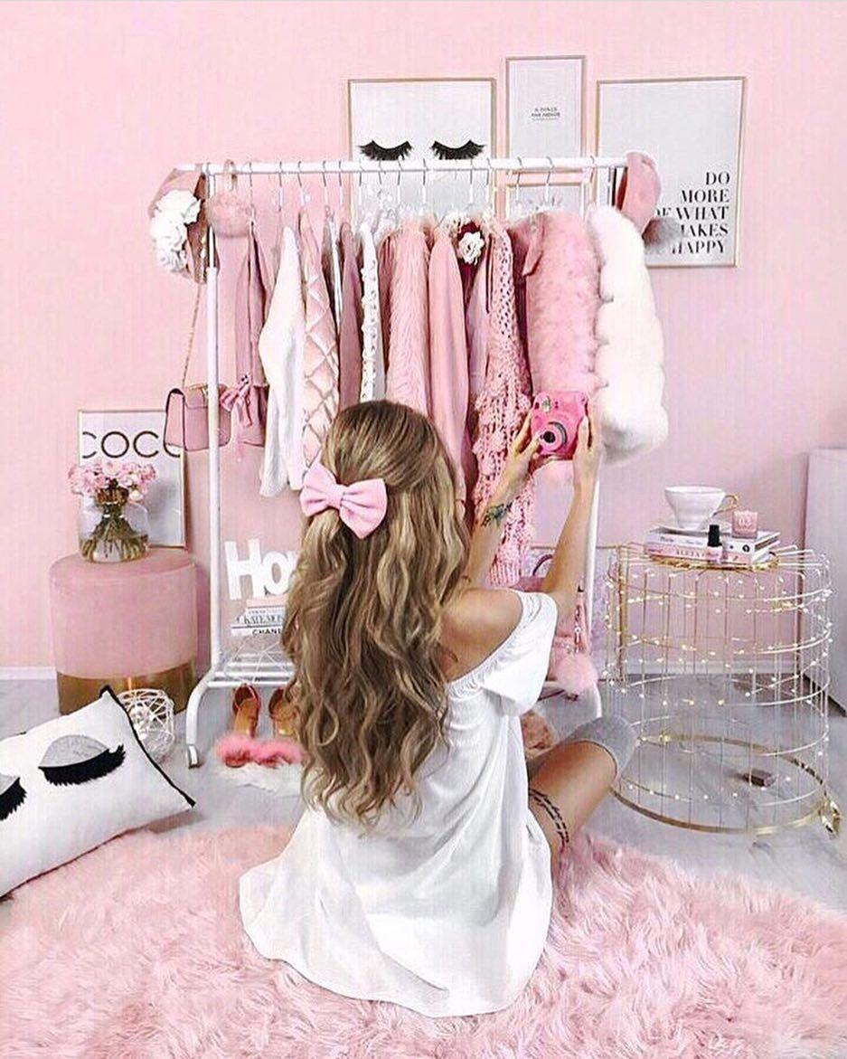 The girl' s wardrobe. All pink shades. Longhaired beauty choosing the morning look