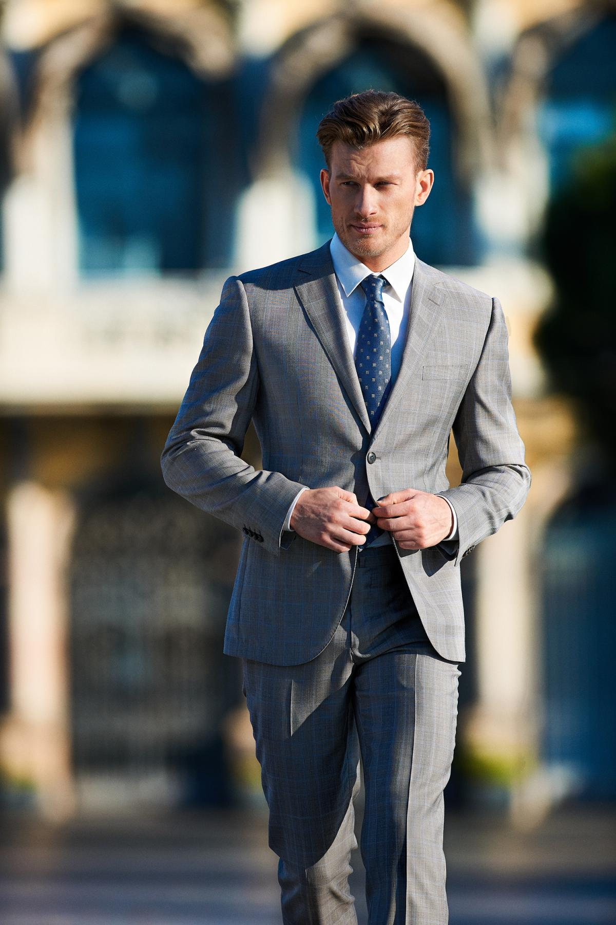 Classic combination of grey suit, white shirt and blue blue tie