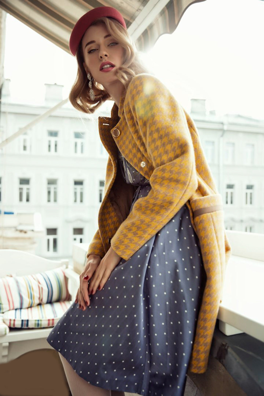 Style of 70th. Yellow coat and blue dress in dotted pattern for spring-summer season